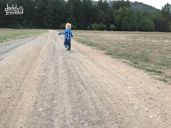 Toddler running on country road.