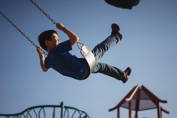 Boy swinging on a chain swing set