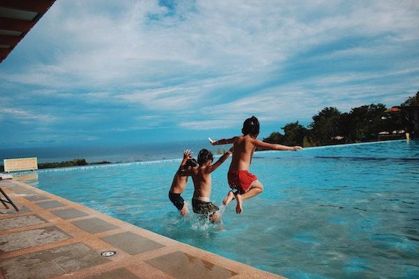 Kids jumping into backyard pool
