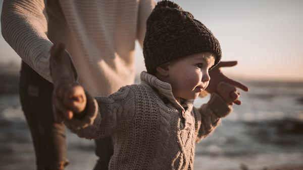 Boy running with parent on beach