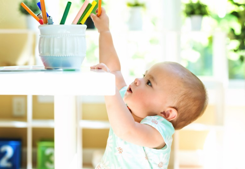 Baby girl reaching for markers on table