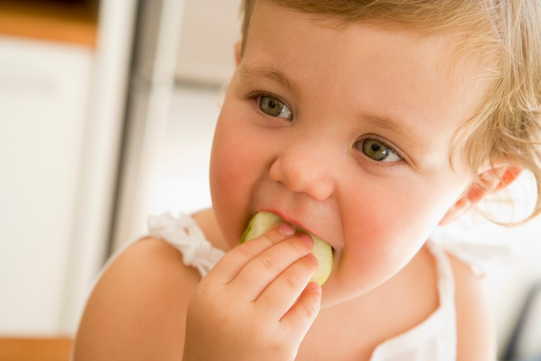 Young baby girl named Piper eating an apple