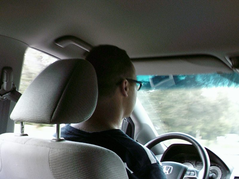 image from the backseat of a man driving a van