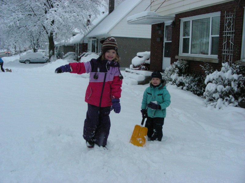Image of two children in snowsuits standing in the snow