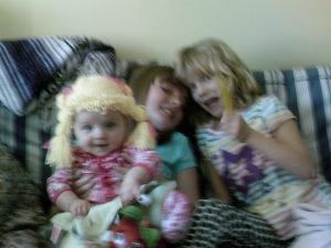 three girls piled on a couch