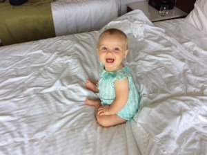 happy baby sitting on a bed