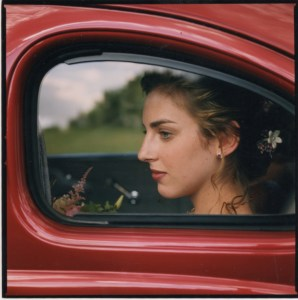 Image of a beautiful bride through the window of an old car