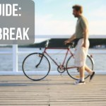 """Image of a man walking a bike on a boardwalk with text """"Dad Guide: Take a Break"""""""