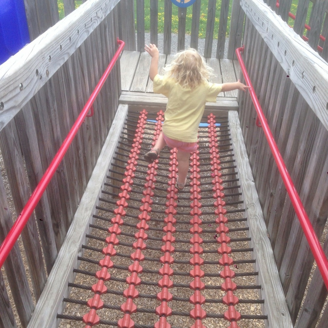 Image of a girl running across a rope bridge