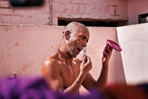 Man shaving, hand held mirror