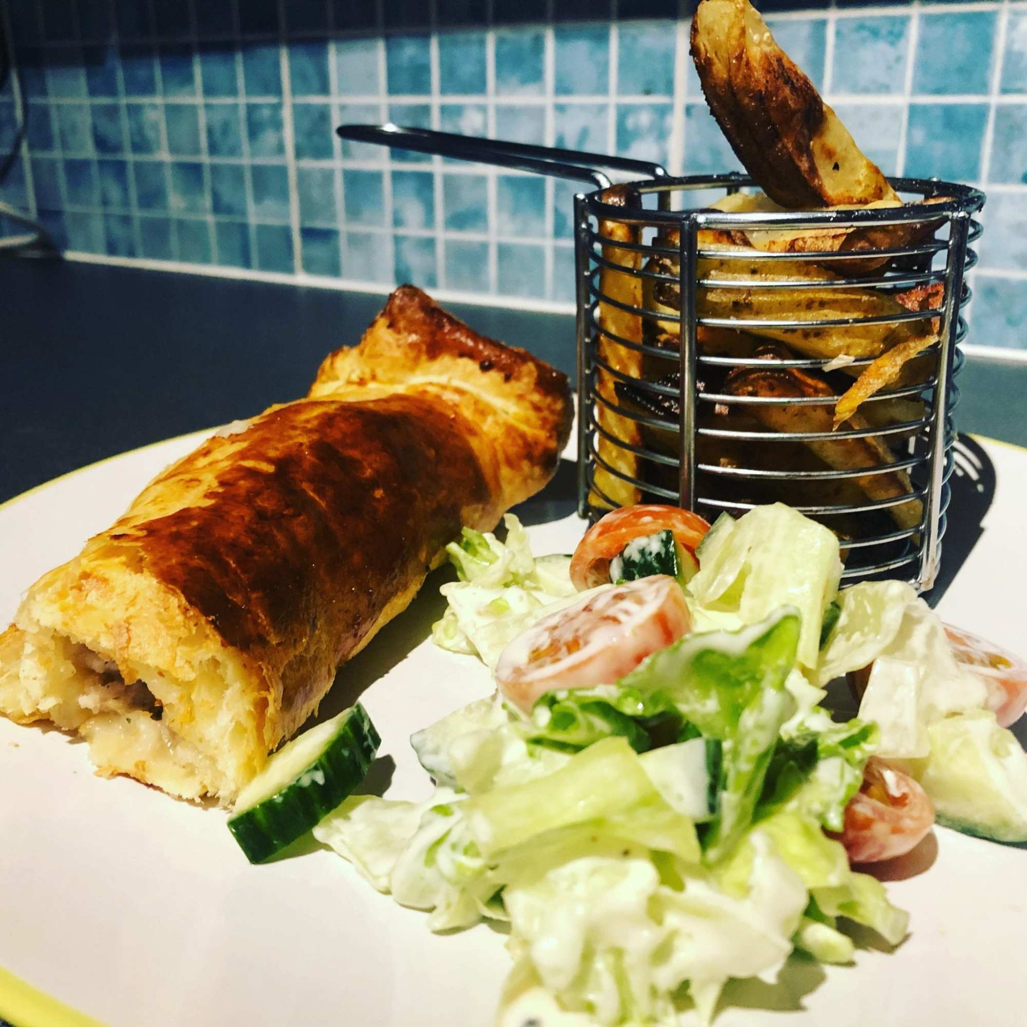 Homemade sausage roll served with potato wedges and side salad