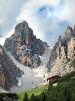 """Ampezzo Dolomitleri'nin Cristallino (3008m) zirvesinin sağında Lorenzi Dağ Evi'ne giden telesiyej, solundaysa kütlenin yamaçlarını yan geçişlerle dolaşan Ivano Dibona metal emniyet hattının (via ferrata) kaçışı olarak muzipçe """"Cortina'ya kestirme!"""" tabelasıyla işaretlenmiş çarşak görünüyor. Botlarını tekrar kullanmak isteyen veya altından akan çarşağın yaşatacağı sinir harbini gözü kesmeyen ziyaretçilerce pek tercih edilen bir kestirme değil!"""