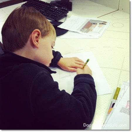 boy drawing kitchen layout at Ikea