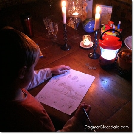 Hurricane Sandy: boy drawing by candlelight