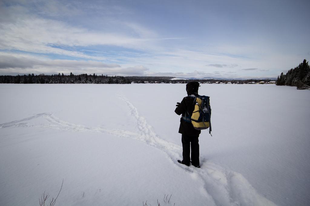Promeneur sur un lac gelé et couvert de neige.