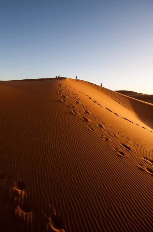 Des touristes au loin sur une dune de Merzouga, sous le coucher du soleil.