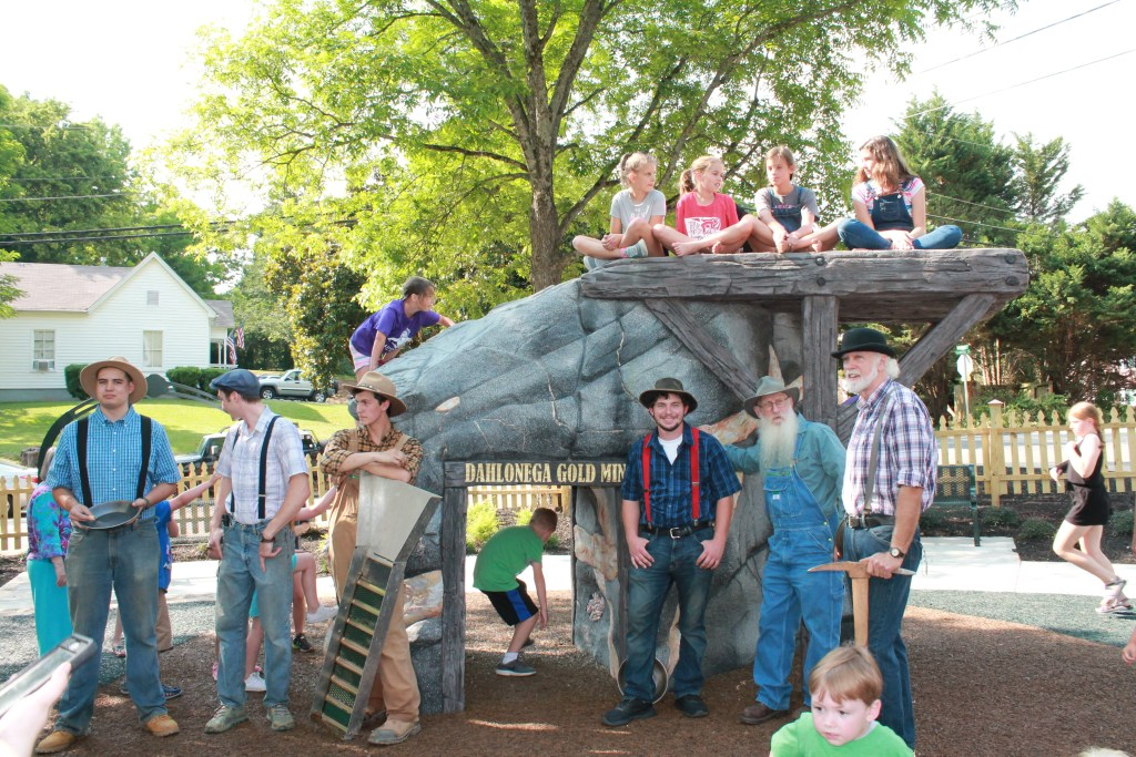 Men dresses as miners stand inf front of the 6' mine shaft climbing structure painted to resemble the rocks found in actual Dahlonega-area gold mines. Children sit on top of the mine.