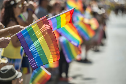 GayPride spectators carrying Rainbow gay flags during Montreal Pride Parade