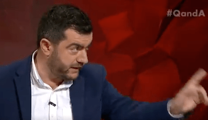 Sam Dastyari eats a brown sandwich