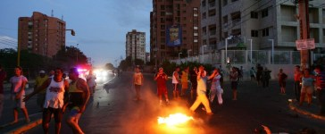 People burn a tyre as they block a road in protest after a large blackout affected five states in Venezuela, in the western city of Maracaibo June 11, 2011. Widespread blackouts have become a major issue ahead of the 2012 presidential vote when President Hugo Chavez hopes to win re-election, both by creating widespread public aggravation and potentially hindering a fragile economic recovery. REUTERS/Isaac Urrutia (VENEZUELA - Tags: POLITICS ENERGY CIVIL UNREST) - RTR2NKQU