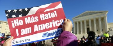 A protester holds a sign as immigrants and community leaders rally in front of the U.S. Supreme Court to mark the one-year anniversary of President Barack Obama's executive orders on immigration in Washington, in this file photo taken November 20, 2015. REUTERS/Kevin Lamarque/Files
