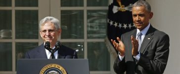 Judge Merrick Garland speaks at the podium as U.S. President Barack Obama applauds after Obama announced him as his nominee to the U.S. Supreme Court, in the Rose Garden of the White House in Washington D.C., March 16, 2016. REUTERS/Kevin Lamarque/File photo