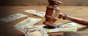 A gavel rests atop a wad of $100 bills. (Photo: AVN Photo Lab/Shutterstock)