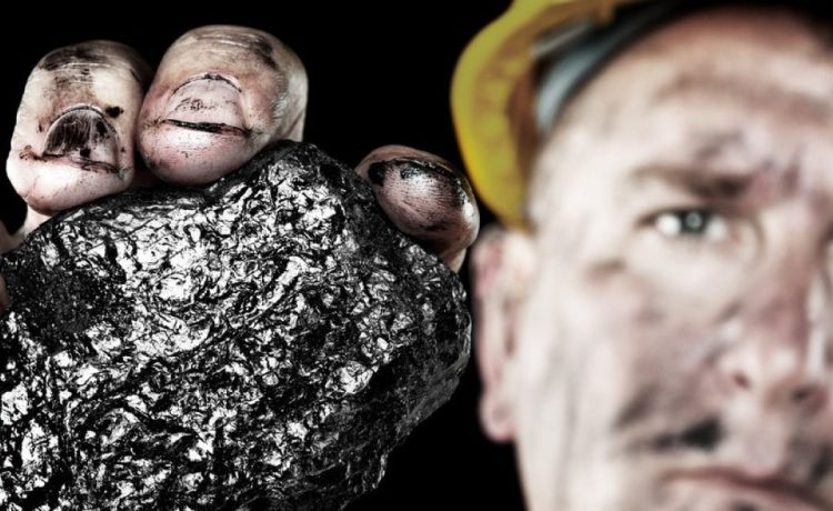 A dirty coalminer displays a lump of coal as a power and energy source. Shutterstock/Joe Belanger