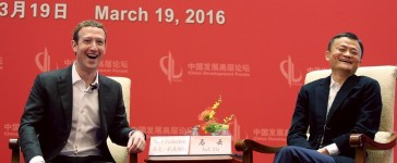 Facebook founder and CEO Mark Zuckerberg and Founder and Executive Chairman of Alibaba Group Jack Ma laugh as they meet at the China Development Forum in Beijing