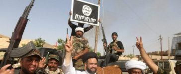 Shi'ite fighters hold an image of the Islamic State flag after clashes with IS militants in Saqlawiya, north of Falluja, Iraq, June 4, 2016. REUTERS/Stringer