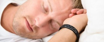 Close-up Of Young Man Sleeping Wearing Smart Wristband [Shutterstock - Andrey_Popov]