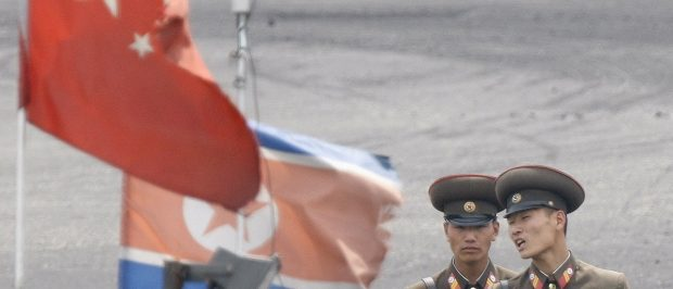 North Korean soldiers chat as they stand guard behind national flags of China (front) and North Korea on a boat anchored along the banks of Yalu River, near the North Korean town of Sinuiju, opposite the Chinese border city of Dandong, June 10, 2013. REUTERS/Jacky Chen