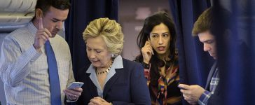 Hillary Clinton looks at national press secretary Brian Fallon's smart phone while on her plane with aid Huma Abedin and traveling press secretary Nick Merrill (Getty Images)