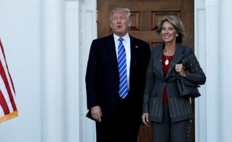 U.S. President-elect Donald Trump (L) stands with Betsy DeVos after their meeting at the main clubhouse at Trump National Golf Club in Bedminster, New Jersey, U.S., November 19, 2016. REUTERS/Mike Segar