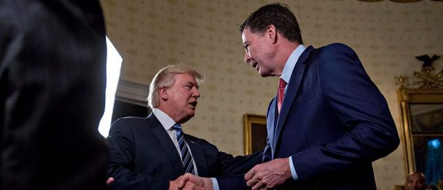 President Donald Trump shakes hands with James Comey, director of the Federal Bureau of Investigation, during an Inaugural Law Enforcement Officers and First Responders Reception in the Blue Room of the White House on January 22, 2017 in Washington, D.C. (Photo by Andrew Harrer-Pool/Getty Images)