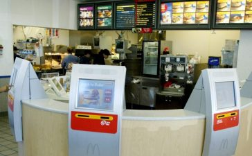 Computer terminals called kiosks line the counter at a McDonalds restaurant in the Denver suburb of Littleton, Colorado July 10, 2003. The system which uses touch screens for customers to make their selections is being tested in the Denver area and could become standard at many of McDonald's worldwide locations. REUTERS/Rick Wilking