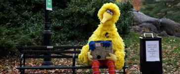A man dressed as the Sesame Street character Big Bird sits on a bench. U.S., November 14, 2016. REUTERS/Shannon Stapleton