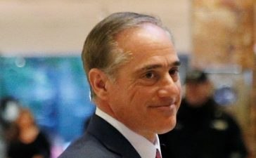 David Shulkin, Under Secretary of Health for the U.S. Department of Veterans Affairs, waves to a reporter after meeting in the lobby of Trump Tower in Manhattan, New York