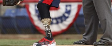 Wounded Warrior Amputee Softball Team catcher Ferreira awaits a pitch during their gamein Binghamton