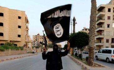 FILE PHOTO: A member loyal to the Islamic State in Iraq and the Levant (ISIL) waves an ISIL flag in Raqqa June 29, 2014. REUTERS/Stringer/File Photo