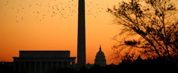 Birds are silhouetted as they fly over the Lincoln Memorial, the Washington Monument and the U.S. Capitol at sunrise on election day in Washington November 8, 2016. REUTERS/Kevin Lamarque