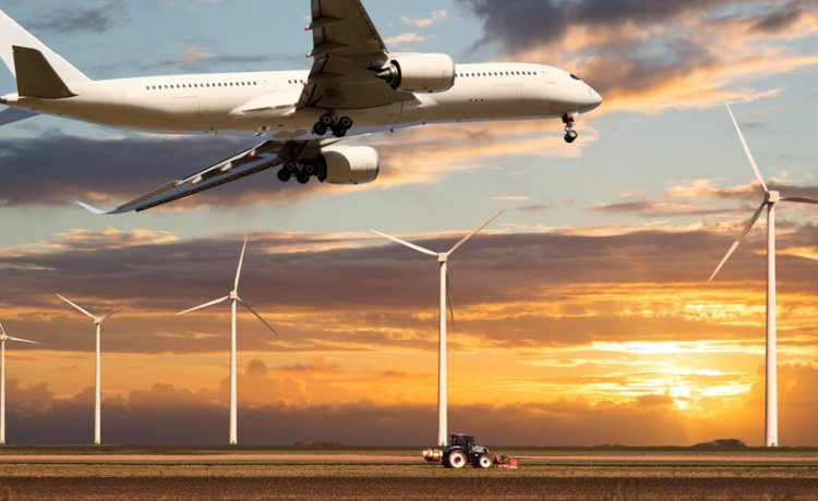 Passenger wide body plane flies low over a field and wind electric generators. The aircraft is climbing against the background of a colorful sunset sky. (Shutterstock/Alexey Y. Petrov)