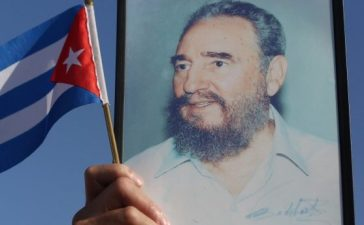 A man holds a Cuban flag in front of a picture of Cuba's late President Fidel Castro during a May Day rally in Havana, Cuba, May 1, 2017. REUTERS/Alexandre Meneghini