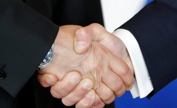 French President Emmanuel Macron (R) shakes hands Russian President Vladimir Putin (L) at the Chateau de Versailles as they meet for talks before the opening of an exhibition marking 300 years of diplomatic ties between the two countries in Versailles, France, May 29, 2017. REUTERS/Philippe Wojazer