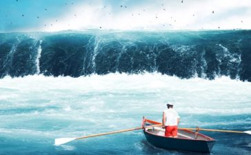 Man on a boat facing a huge wave. [Shutterstock - frankie's]