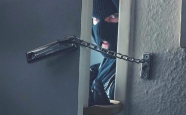 Dangerous masked burglar with crowbar breaking into a victim's home. [Shutterstock - r.classen]