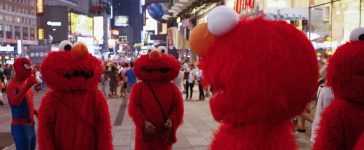 "Jorge, an immigrant from Mexico (C), stands amidst other people, all dressed as the Sesame Street character Elmo, while they look to make tips for photographs in Times Square in New York July 30, 2014. Elmo and Cookie Monster have long delighted young viewers on TV's ""Sesame Street,"" but the recent antics of New York street performers dressed as the beloved characters have drawn the ire of city officials and now the show's producers. Sesame Workshop, which owns the rights to Big Bird, Ernie and the assorted puppet monsters on the 45-year-old program, said on July 29, 2014 it was drafting plans to stop performers who dress up as the characters from appearing in Times Square, where they pose for photos with tourists and then demand tips. Picture taken July 30, 2014. To match story USA-SESAME STREET/NEW YORK REUTERS/Eduardo Munoz (UNITED STATES - Tags: ENTERTAINMENT SOCIETY TPX IMAGES OF THE DAY) - RTR40UDD"