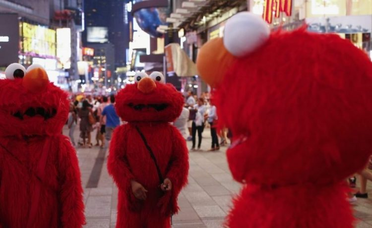 """Jorge, an immigrant from Mexico (C), stands amidst other people, all dressed as the Sesame Street character Elmo, while they look to make tips for photographs in Times Square in New York July 30, 2014. Elmo and Cookie Monster have long delighted young viewers on TV's """"Sesame Street,"""" but the recent antics of New York street performers dressed as the beloved characters have drawn the ire of city officials and now the show's producers. Sesame Workshop, which owns the rights to Big Bird, Ernie and the assorted puppet monsters on the 45-year-old program, said on July 29, 2014 it was drafting plans to stop performers who dress up as the characters from appearing in Times Square, where they pose for photos with tourists and then demand tips. Picture taken July 30, 2014. To match story USA-SESAME STREET/NEW YORK REUTERS/Eduardo Munoz (UNITED STATES - Tags: ENTERTAINMENT SOCIETY TPX IMAGES OF THE DAY) - RTR40UDD"""