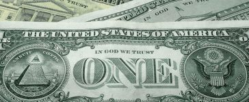 """WASHINGTON - OCTOBER 14: The words """"In God We Trust"""" are seen on U.S. currency October 14, 2004 in Washington, DC. Although the U.S. constitution prohibits an official state religion, references to God appear on American money, the U.S. Congress starts its daily session with a prayer, and the same U.S. Supreme Court that has consistently struck down organized prayer in public schools as unconstitutional opens its public sessions by asking for the blessings of God. The Supreme Court will soon use cases from Kentucky and Texas to consider the constitutionality of Ten Commandments displays on government property, addressing a church-state issue that has ignited controversy around the country. (Photo Illustration by Alex Wong/Getty Images)"""