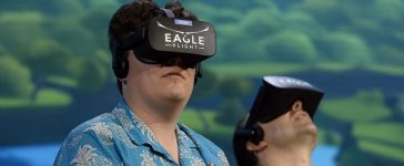 """Palmer Luckey, co-founder of Oculus VR Inc., left, plays the new video game """"Eagle Flight VR"""" during an Ubisoft news conference before the start of the E3 Gaming Conference on June 13, 2016 in Los Angeles, California. (PHOTO: Kevork Djansezian/Getty Images)"""